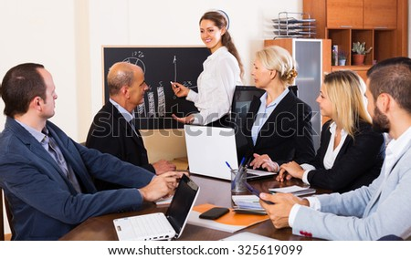 Successful positive adult business people during conference call indoors