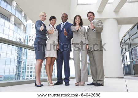 Successful positive interracial group of business men & women, businessmen and businesswomen team, giving thumbs up - stock photo