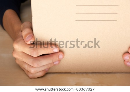 Successful Postal or delivery service concept. Man holding cardboard box with two arms on table - stock photo
