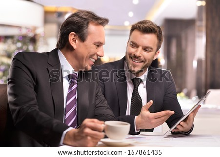 Successful project. Two cheerful business people in formalwear discussing something and smiling while one of them pointing digital tablet - stock photo