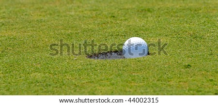 Successful putt as golf ball falls into hole - stock photo