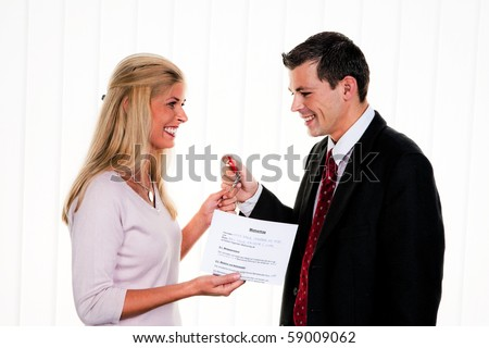 Successful real estate broker with a house key - stock photo