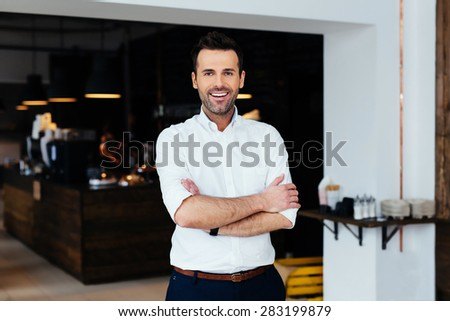 Successful restaurant manager standing with crossed arms - stock photo