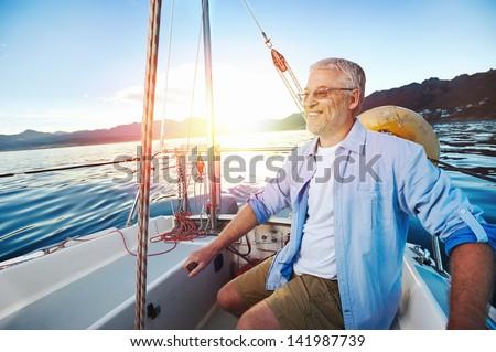successful retired man sailing portrait at sunrise on boat - stock photo