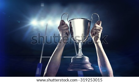 Successful rugby player holding trophy against rugby stadium - stock photo