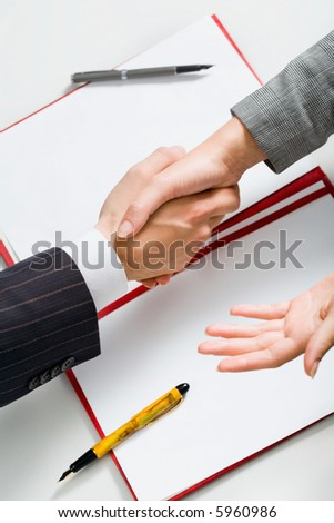Successful sale: business handshake with paper, folder, two pens in the background - stock photo