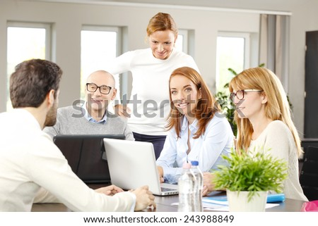 Successful sales team sitting at meeting while they working on laptop. - stock photo