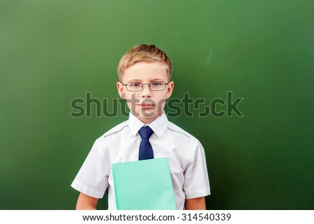 Successful schoolboy standing near the blackboard in a school classroom, dressed in a school uniform and sunglasses - stock photo