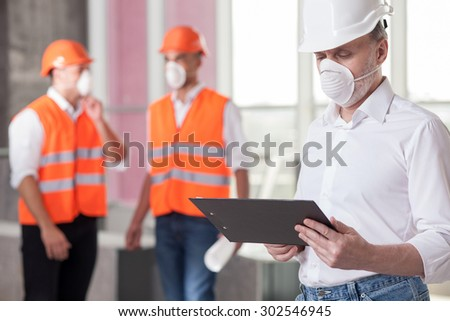 Successful senior architect is holding the folder and reading documents with concentration. The workers are standing behind his and discussing the building. They are wearing masks and helmets - stock photo