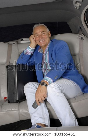 Successful senior businessman inside a car holding a phone. - stock photo