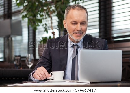 Successful senior businessman is using a laptop in restaurant. He is drinking coffee and smiling. The man is looking at the screen with joy