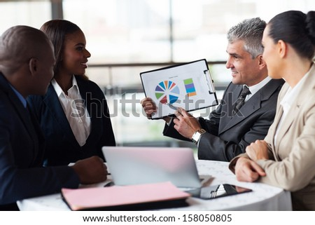 successful senior businessman showing a graph to his business team - stock photo