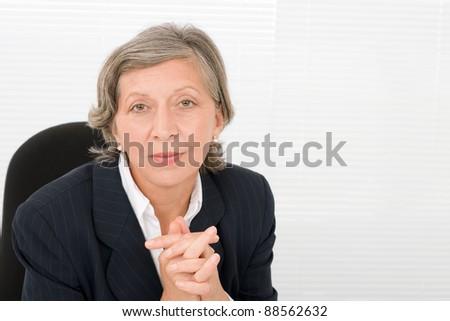 Successful senior businesswoman professional portrait watch camera - stock photo