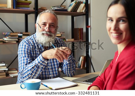 successful senior man and young woman looking at camera in office - stock photo