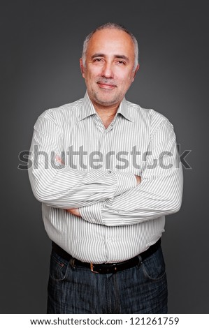successful senior man with folded hands standing over grey background - stock photo