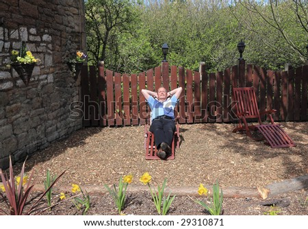 Successful Senior taking a break to relax in the Sun at the bottom of The Garden - stock photo