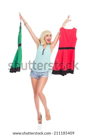 Successful shopping. Excited blond young woman holding green and red dress. Full length studio shot isolated on white. - stock photo