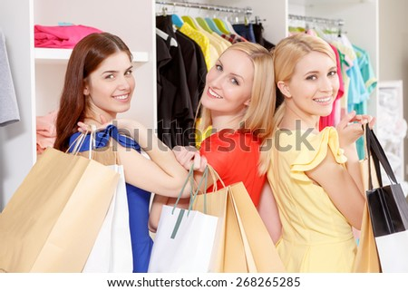 Successful shopping. Three young beautiful women turning happily back holding paper bags copyspace in a fashion store