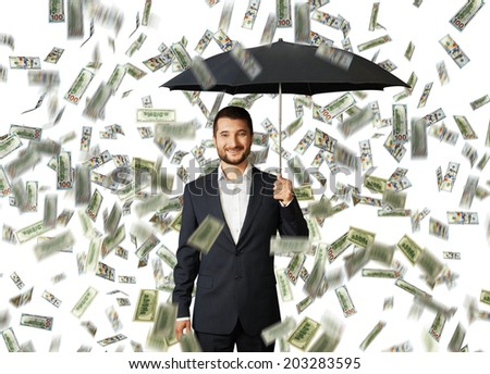 successful smiley businessman with black umbrella standing under money rain - stock photo