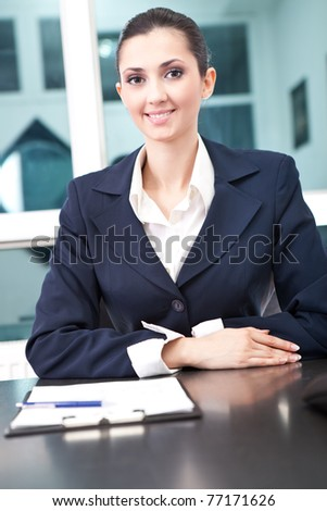 successful, smiling business woman in her office, looking in camera - stock photo