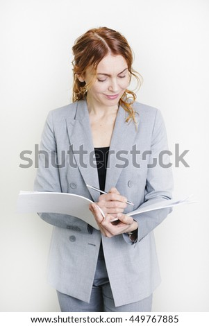 Successful smiling business woman making notes in her work papers - stock photo