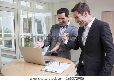 Successful smiling businessmen in office, with arms up  - stock photo