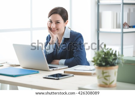 Successful smiling businesswoman posing in her office, she is sitting at desk and working with a laptop, women's entrepreneurship concept - stock photo