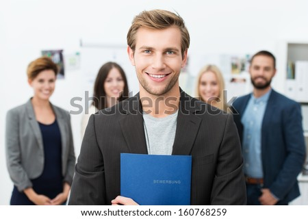 Successful smiling young male job applicant holding a blue file with his curriculum vitae posing in front of his new work colleagues or business team - stock photo