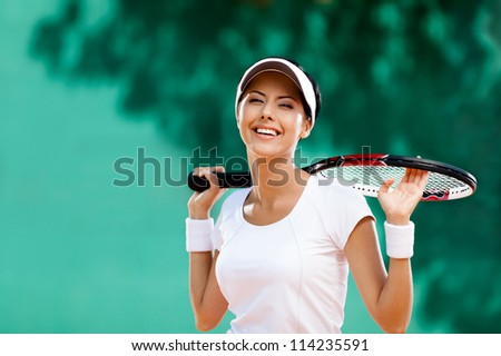 Successful sportswoman with racket at the tennis court. Healthy lifestyle - stock photo