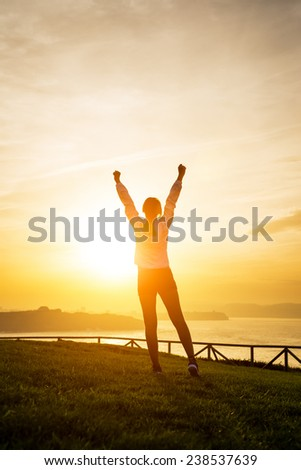 Successful sporty woman raising arms towards golden beautiful sunset and sea. Female athlete celebrating sport success and goals. Healthy lifestyle concept. - stock photo