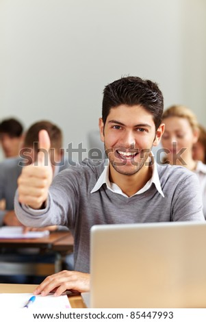 Successful student at laptop holding his thumbs up - stock photo