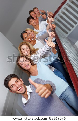 Successful students at university holding their thumbs up - stock photo