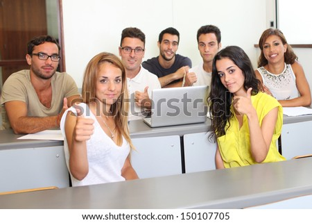 Successful students holding thumbs up - stock photo