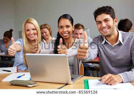 Successful students in class holding thumbs up - stock photo