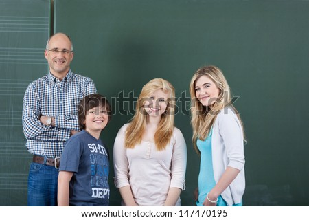 Successful team at school with a smiling confident male teacher posing with two teenage girls and boy from his class in front of the blackboard - stock photo