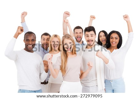 Successful team. Group of happy young people in smart casual wear looking at camera and keeping arms raised while standing against white background - stock photo