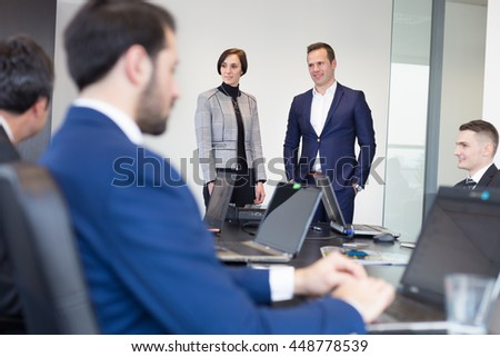 Successful team leader and business owner  leading informal in-house business meeting. Businessman working on laptop in foreground. Business and entrepreneurship concept. - stock photo