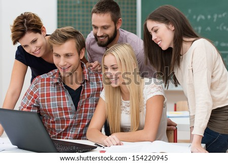 Successful team of diverse young male and female students in the classroom smiling with delight as they read the outcome of their project on a laptop computer