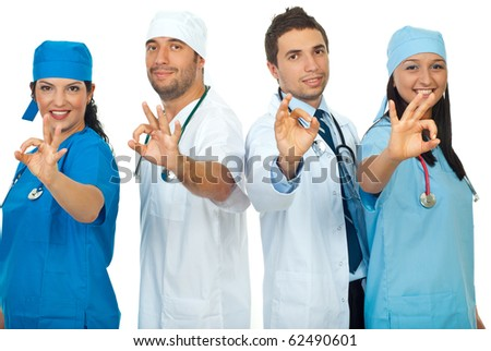 Successful team of doctors showing okay sign hand and standing in a row  isolated on white background - stock photo