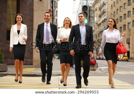 Successful Team of five business people confidently striding along the summer street - stock photo