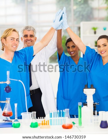 successful team of scientists high five in lab - stock photo