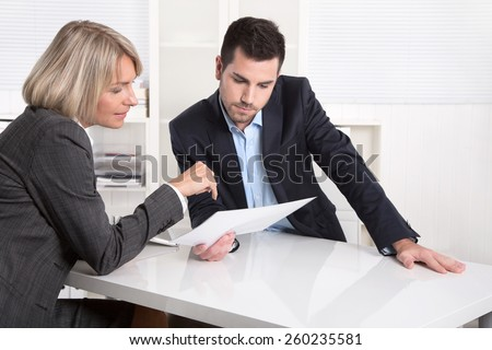 Successful teamwork: business man and woman sitting at desk talking about reports and finance. - stock photo
