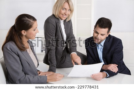 Successful teamwork: career businesswoman and businessman sitting around a table talking together in a meeting.