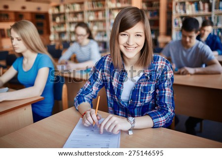 Successful teenager sitting by desk in college - stock photo