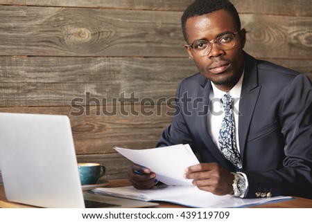 Successful top-manager sitting, working with papers and computer in comfortable café. Elegant official suit, wristwatches and happy look of African businessman say he is pleased with productive job. - stock photo