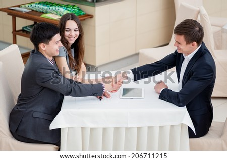 Successful transaction. Three successful businessmen discussing business in the restaurant sitting at the table. Man and woman came to the meeting with the boss. Young people work for your tablet - stock photo