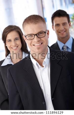 Successful trendy young businessteam, standing together, smiling at camera confidently.
