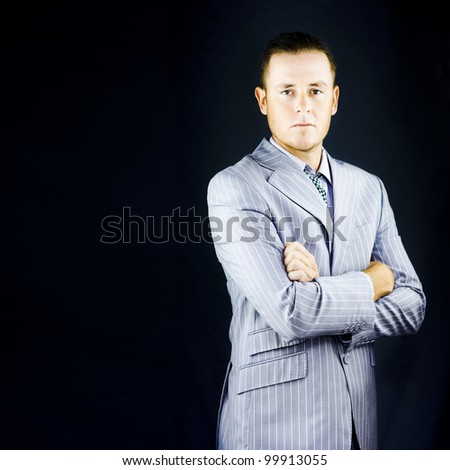 Successful wealthy influential young business man posing in a bespoke pinstripe suit with an air of authority and self-assurance against a dark background - stock photo
