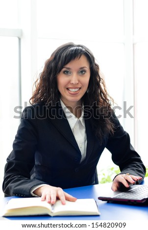 Successful woman at office workplace with mobile cell phone happy smiling & looking at camera