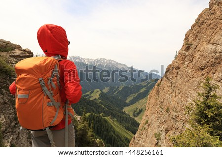successful woman backpacker hiking on mountain peak cliff